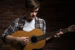 Attraktiv ung gitarrist som spelar den akustiska gitarren arkivbilder