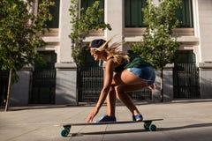 Attraktiv ung gladlynt kvinna med en skateboard Royaltyfria Foton