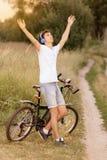 Attraktiv ung grabb med vägcykeln utomhus Royaltyfri Bild