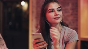 Attraktiv ung kvinna för ung kvinna med hörlurar i hennes öron som lyssnar till musik och använder smartphonen Suddig natt arkivfilmer