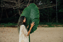 Attraktiv ung kvinna för stående på träd för stort grönt blad för bakgrund tropiskt arkivbilder