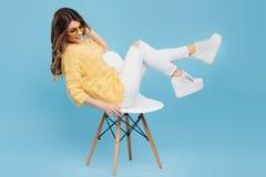 Attraktiv ung kvinna i den gula tröjan som poserar på blå bakgrund Nätt flicka i gula exponeringsglas Fotografering för Bildbyråer