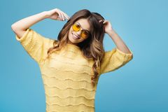 Attraktiv ung kvinna i den gula tröjan som poserar på blå bakgrund Nätt flicka i gula exponeringsglas Royaltyfri Foto