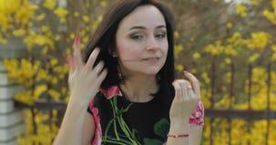 Attraktiv ung kvinna i en klänning med blommor som gör roliga framsidor arkivfilmer