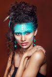 Attraktiv ung kvinna i etniska smycken tät stående upp Härlig flickamedicinman Stående av en kvinna med en målad framsida Arkivbilder