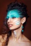 Attraktiv ung kvinna i etniska smycken tät stående upp Härlig flickamedicinman Stående av en kvinna med en målad framsida Royaltyfri Foto