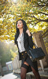 Attraktiv ung kvinna i ett höstligt modeskott Den härliga trendiga damen i den svartvita dräkten som in poserar, parkerar Arkivbild