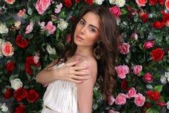 Attraktiv ung kvinna i flott vit klänning på blommaväggen royaltyfria bilder