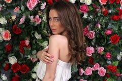 Attraktiv ung kvinna i flott vit klänning på blommaväggen royaltyfri foto