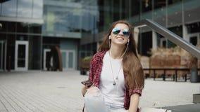 Attraktiv ung kvinna i märkta exponeringsglas som vinkar hennes hand arkivfilmer