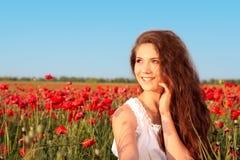 Attraktiv ung kvinna i vallmofält Arkivfoto