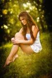 Attraktiv ung kvinna i vitt kort klänningsammanträde på gräs i en solig sommardag härlig tyckande om flickanatur Arkivbilder