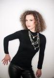 Attraktiv ung kvinna med den svarta halvpolokrageblusen mot den vita väggen Gullig flicka med långt lockigt hår i svart dräkt Arkivfoto