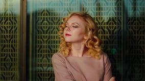 Attraktiv ung kvinna med den vita dagsljusstaden för lockigt hår på bakgrund arkivfilmer