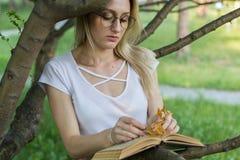 Attraktiv ung kvinna med en bok i händerna i parkerabenägenheten på en trädfilial Arkivbilder