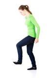 Attraktiv ung kvinna med ett ben upp. Sidosikt. Arkivfoton