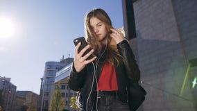 Attraktiv ung kvinna med långt hår i hörlurar genom att använda smartphonen, medan gå på den stads- gatabakgrunden lager videofilmer