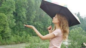 Attraktiv ung kvinna med paraplyet under vårregnet på grön skogbakgrund Flickan bär den rosa klänningen och lager videofilmer