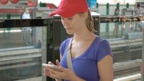 Attraktiv ung kvinna på station för overgroundgångtunneltunnelbana som kontrollerar hennes väntande drev för telefon för att anko stock video