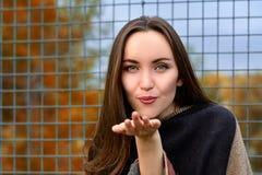 Attraktiv ung kvinna som överför en kyss Hösten landskap Fotografering för Bildbyråer