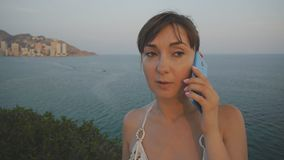 Attraktiv ung kvinna som använder smartphonen Den härliga flickan som talar på telefonen på sommarsolnedgångsjösidan, höjde balko lager videofilmer