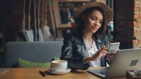 Attraktiv ung kvinna som använder smartphonen i kafét som tycker om socialt le för massmedia lager videofilmer