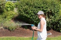 Attraktiv ung kvinna som bevattnar växterna i trädgården Arkivfoto