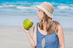 Attraktiv ung kvinna som dricker kokosnötvatten på stranden Royaltyfri Fotografi