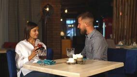 attraktiv ung kvinna som får en gåvaask från hennes pojkvän, medan sitta i kafét lager videofilmer