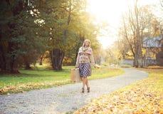 Attraktiv ung kvinna som går med en bukett av höstsidor och en resväska royaltyfria foton
