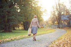 Attraktiv ung kvinna som går med en bukett av höstsidor och en resväska arkivbild
