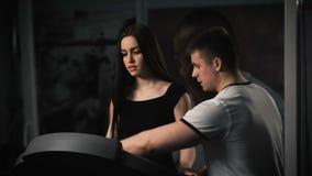 Attraktiv ung kvinna som gör cardio övning på trampkvarnen på idrottshallen stock video