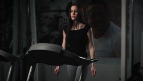 Attraktiv ung kvinna som gör cardio övning på trampkvarnen på idrottshallen arkivfilmer