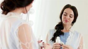 Attraktiv ung kvinna som gör hennes ansiktsbehandling med bomullsbomullstoppen och framme fuktar lotion av spegeln arkivfilmer