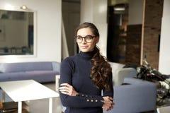 Attraktiv ung kvinna som hänsynsfullt ser och ler, medan stå inomhus arkivbilder