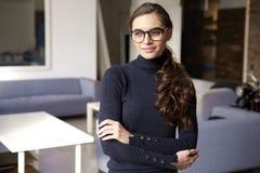 Attraktiv ung kvinna som hänsynsfullt ser och ler, medan stå inomhus royaltyfri fotografi