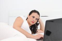 Attraktiv ung kvinna som hemma arbetar på hennes bärbar dator Fotografering för Bildbyråer