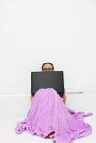 Attraktiv ung kvinna som hemma arbetar på hennes bärbar dator Arkivbild