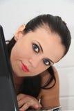 Attraktiv ung kvinna som hemma arbetar på hennes bärbar dator Royaltyfria Bilder
