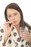 Attraktiv ung kvinna som känner sig bakfull och opasslig tagande medicin Arkivfoto