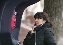 Attraktiv ung kvinna som kallar fr?n en gatapayphone arkivfoto