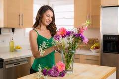 Attraktiv ung kvinna som är lycklig med blommor från hennes förälskad pojkvänvän som är jätteglad och Fotografering för Bildbyråer