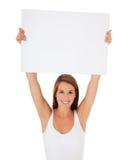 Attraktiv ung kvinna som rymmer det blanka tecknet Arkivbild