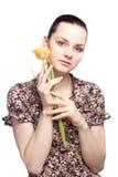 Attraktiv ung kvinna som rymmer en gul tulpan royaltyfria bilder