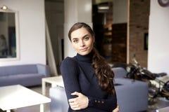 Attraktiv ung kvinna som ser kameran och ler, medan stå inomhus fotografering för bildbyråer
