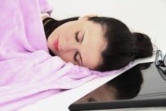 Attraktiv ung kvinna som sover i säng med bärbara datorn Royaltyfria Bilder