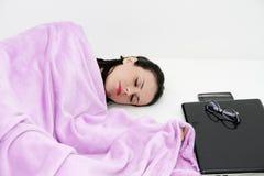 Attraktiv ung kvinna som sover i säng med bärbara datorn Royaltyfri Fotografi