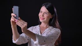 Attraktiv ung kvinna som tar selfie och att le som står isolerade på svart bakgrund arkivfilmer