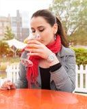 Attraktiv ung kvinna som tycker om coctailen i en utomhus- stång arkivbild
