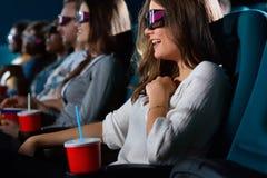 Attraktiv ung kvinna som tycker om filmer på bion Arkivfoto